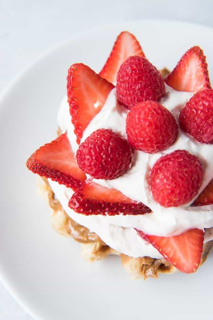 a cream and berry topped waaffle on a white plate
