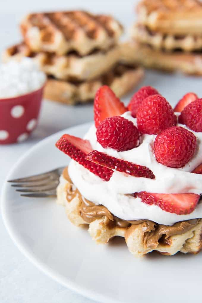 stacks of waffles in the background with a waffle in front covered in spreads and fresh berries