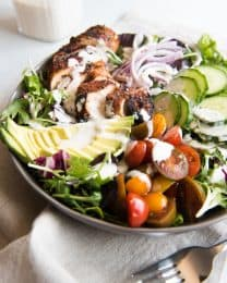 Grilled Cajun Chicken Salad ingredients all in a bowl with dressing drizzled over the top