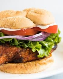 Grilled Cajun Chicken Sandwiches are deliciously spicy with a crispy, blackened crust that forms around the juicy, tender chicken breast when seared over high heat. Then you sandwich the chicken between soft, toasted buns with cool and crispy lettuce, tomatoes, and red onions for a fabulous alternative to your standard burger fare!