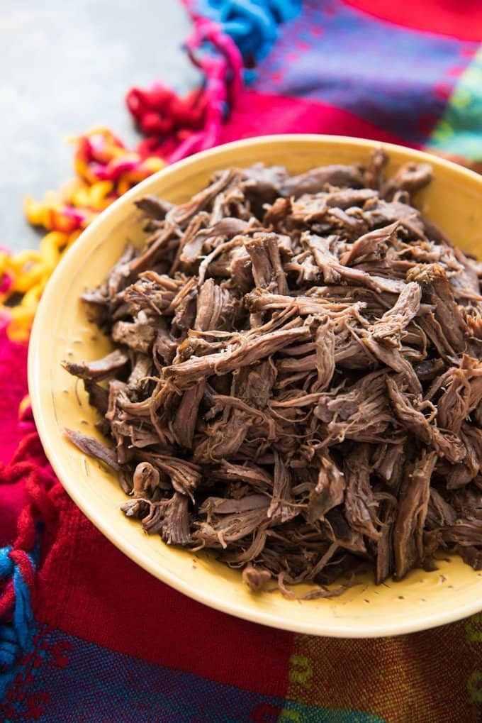 a yellow bowl full of shredded beef on a colorful cloth