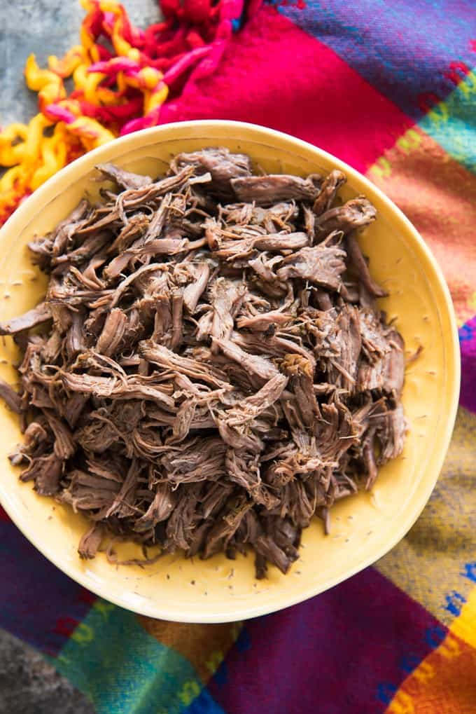 an aerial view of Slow Cooker Mexican Shredded beef in a yellow bowl