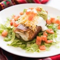 a Chimichangas on a bed of lettuce on a white plate topped with sour cream, guac, tomatoes, and cheese