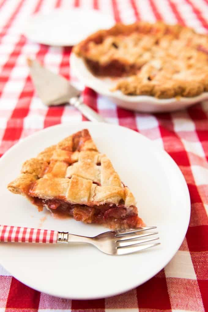 Strawberry Rhubarb Pie slice on a white plate with a fork with more pie in the background