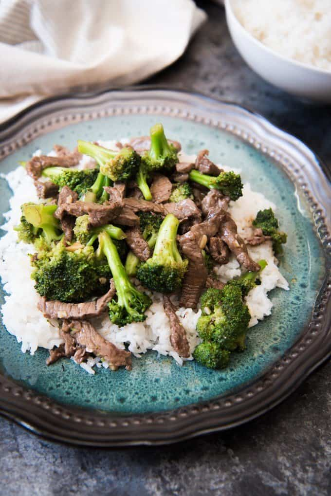 broccoli beef on a bed of rice on a plate