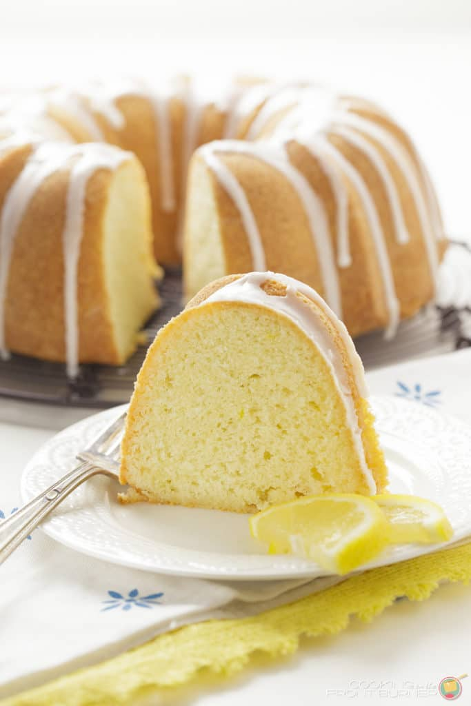 a delicious lemon pound cake with a nice white drizzle of icing. one slice removed and placed on a plate in front with lemon wedges.