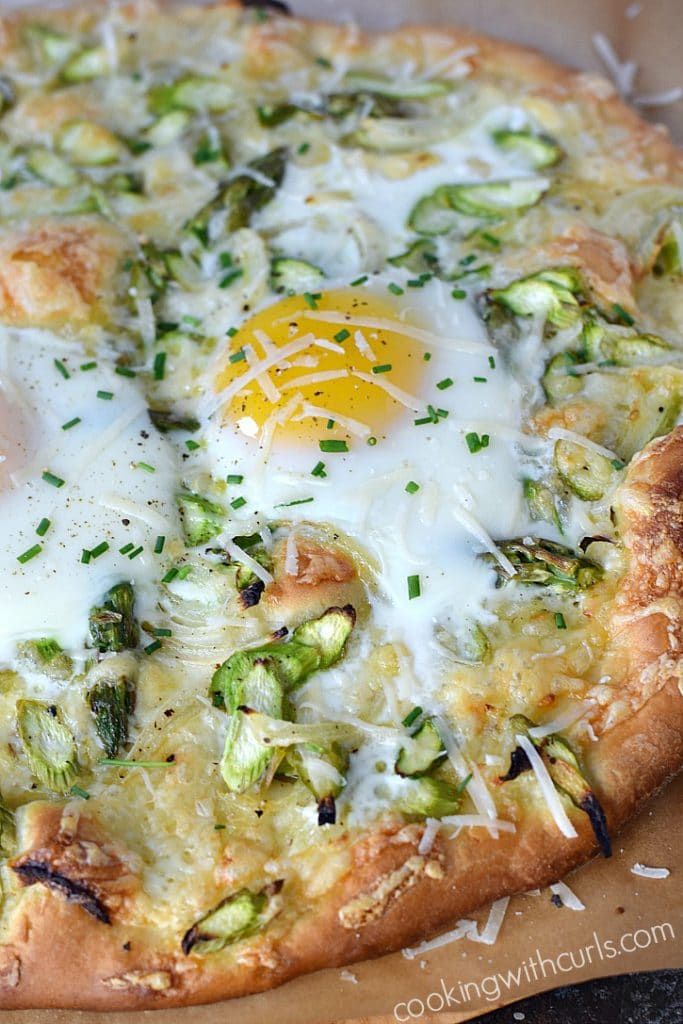 An egg topped asparagus breakfast pizza