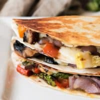 Grilled Summer Vegetable Quesadillas stacked on top of eachother on a white plate