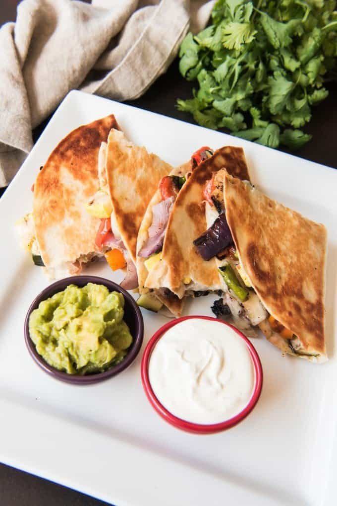 These Grilled Summer Vegetable Quesadillas are an easy, healthy, and delicious vegetarian lunch or dinner and a great way to use up Summer's fresh produce! Loaded with grilled fresh peppers, onions, and mushrooms, then filled with a blend of melted mozzarella and pepperjack cheese, these Grilled Summer Vegetable Quesadillas are a surefire solution to your meatless Monday dinnertime fix!