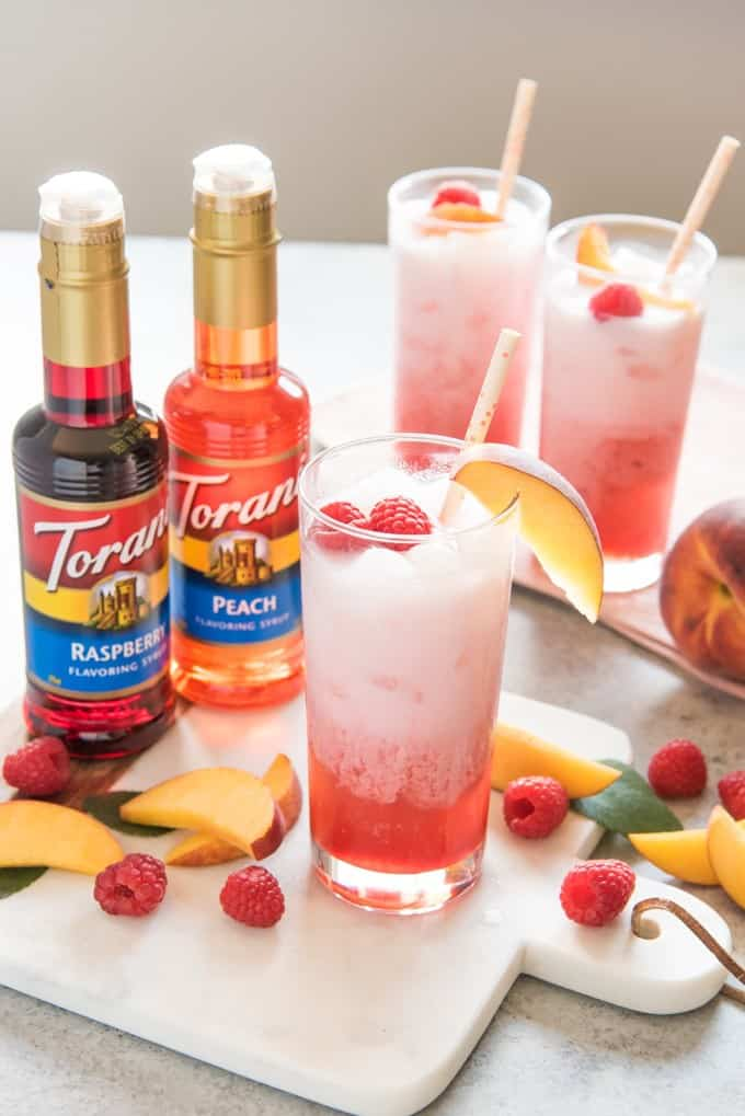 two bottles of torani syrup next to 3 glasses full of freshly made raspberry peach italian soda with fresh raspberries and peached scattered all around and garnishing the cups