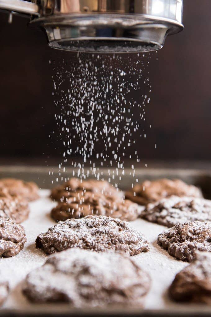 An image of sifting powdered sugar onto chocolate brownie cookies on a baking sheet.