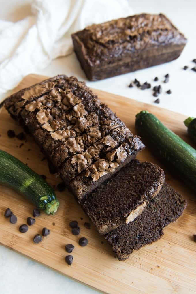 a sliced loaf of double chocolate zucchini bread with a whole slice in the background