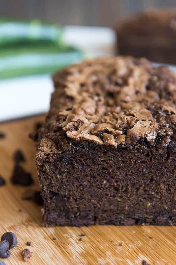 a crumb shot of a double chocolate zucchini bread sliced and on a wooden cutting board