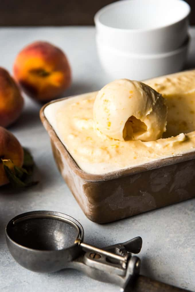 a scoop of fresh peach icecream in a loafpan with a curled scoop and a scooper off to the side