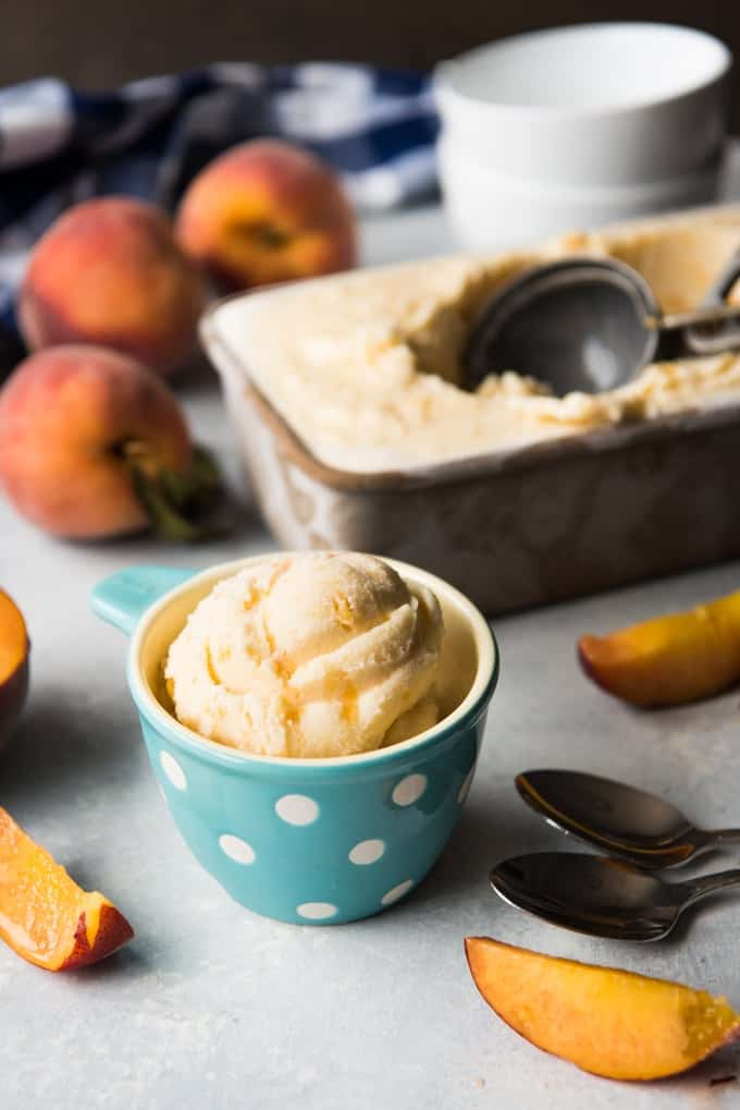 fresh peach ice cream in a loaf pan with a scooper and a scoop in a cup with fresh peaches around it