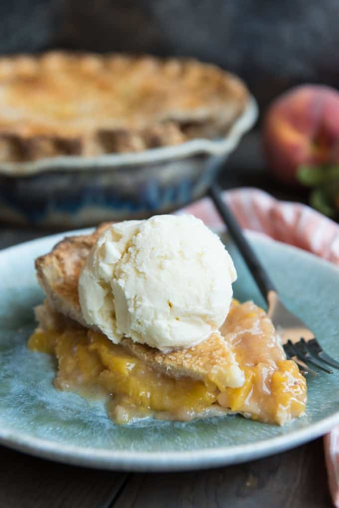 a slice of peach pie on a plate with a scoop of white ice cream on top