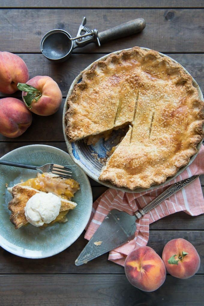an aerial shot of a peach pie with a slice removed and placed on a plate and then topped with ice cream