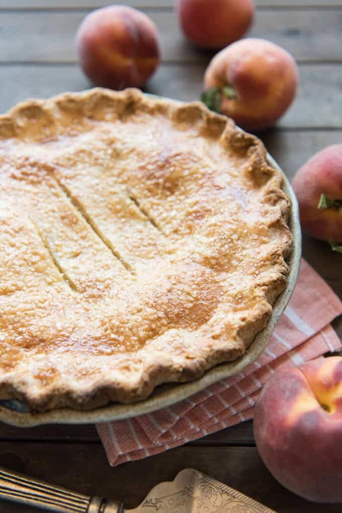 a peach pie next to fresh peaches