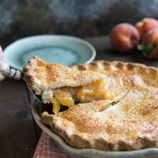 This classic, Southern Peach Pie is absolute dessert perfection! Filled with summer's juiciest, sweetest fresh peaches and made with a flaky, buttery double-crust dusted with sanding sugar, this fresh peach pie is as beautiful as it is delicious and wonderful served à la mode with a big scoop of vanilla ice cream!