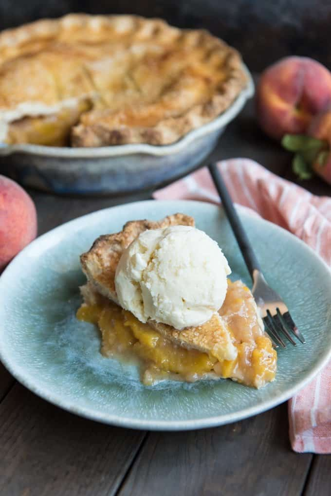 a slice of southern peach pie on a blue plate with ice cream on top and a fork to the side