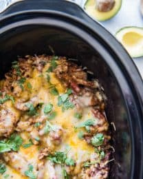 black slow cooker liner filled with melted cheese over flank steak brown rice casserole with an open avocado next to it