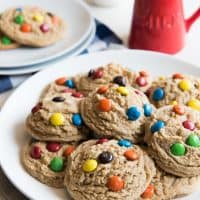 big and soft m&m cookies on ahwite plates with a pitcher of milk to the side
