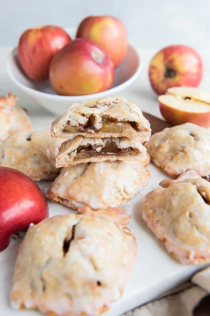 apple hand pies and fresh apples one pie sliced in half and stacked to reveal contents