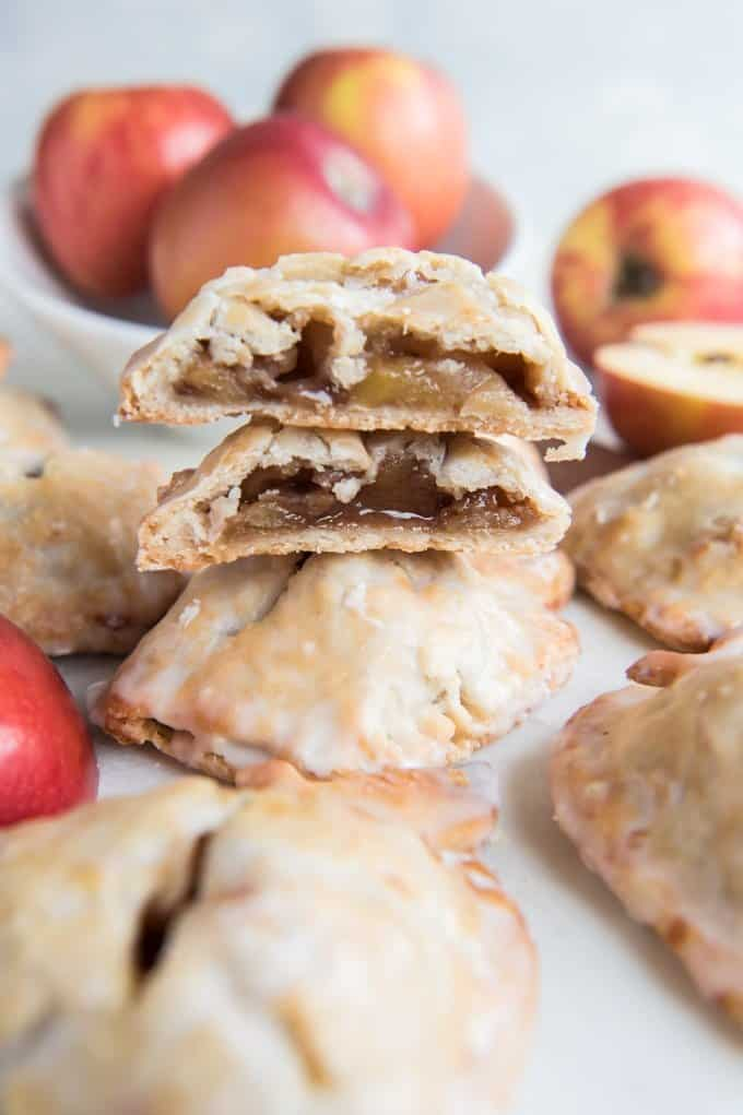 apple hand pies stacked on top of eachother and one sliced to reveal filling inside