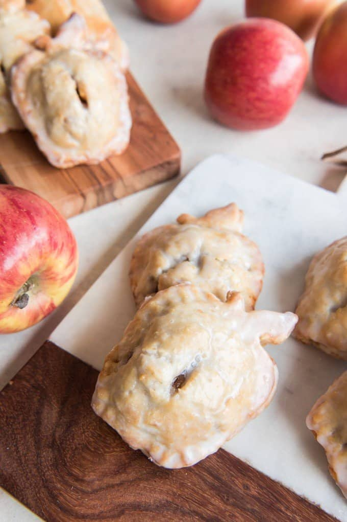 glazed apple pies shaped like apples with fresh apples around them