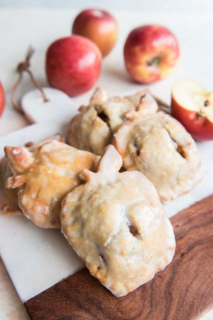 several apple shaped apple pies on a cutting board with apples in the background