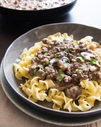 A gray plate contains cooked egg noodles topped with freshly made beef strongaff with mushrooms and a skillet in the background holds more sauce