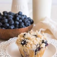 homemade blueberry muffin with streusel topping in front of pitcher of milk and bowl of fresh blueberries