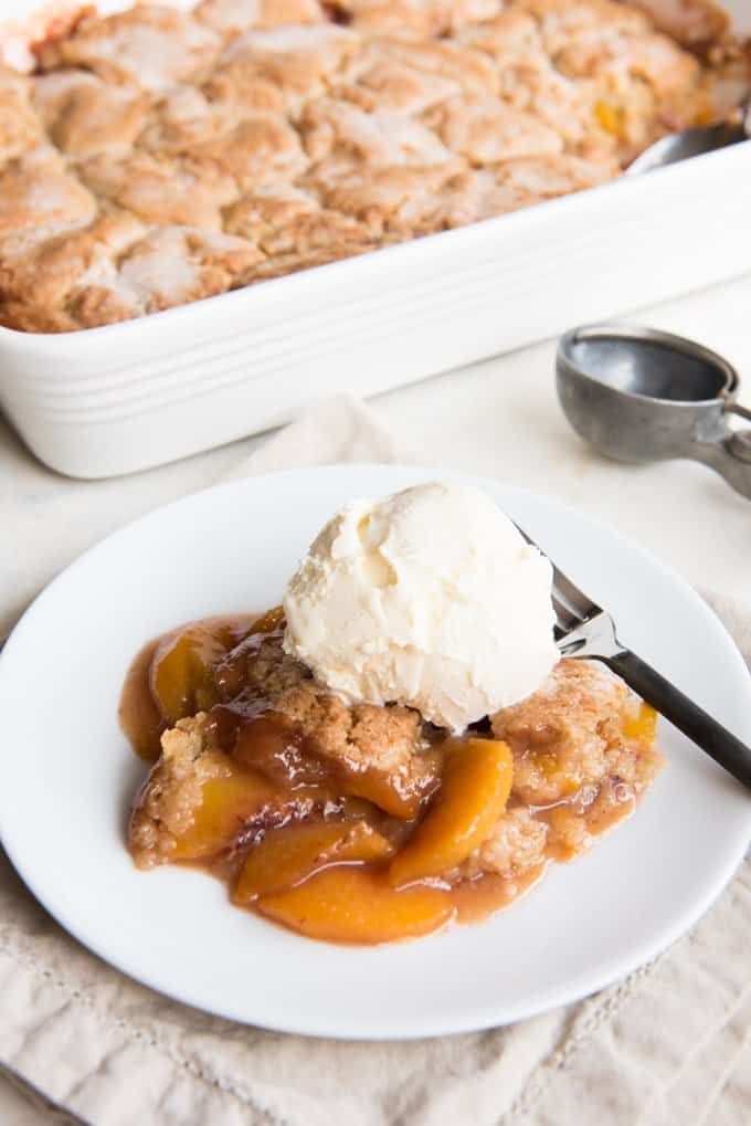 Fresh Peach Cobbler just may be the ultimate summer dessert comfort food.  It's simple, easy and a timeless classic with a buttery cobbler topping, fresh juicy peaches, and hints of cinnamon in a rich, sweet syrup.  This is the best peach cobbler I have ever eaten!  It has a perfectly wonderful crust that is crisp on top but is also soft and moist and chewy thanks to the juicy peaches bubbling below it.