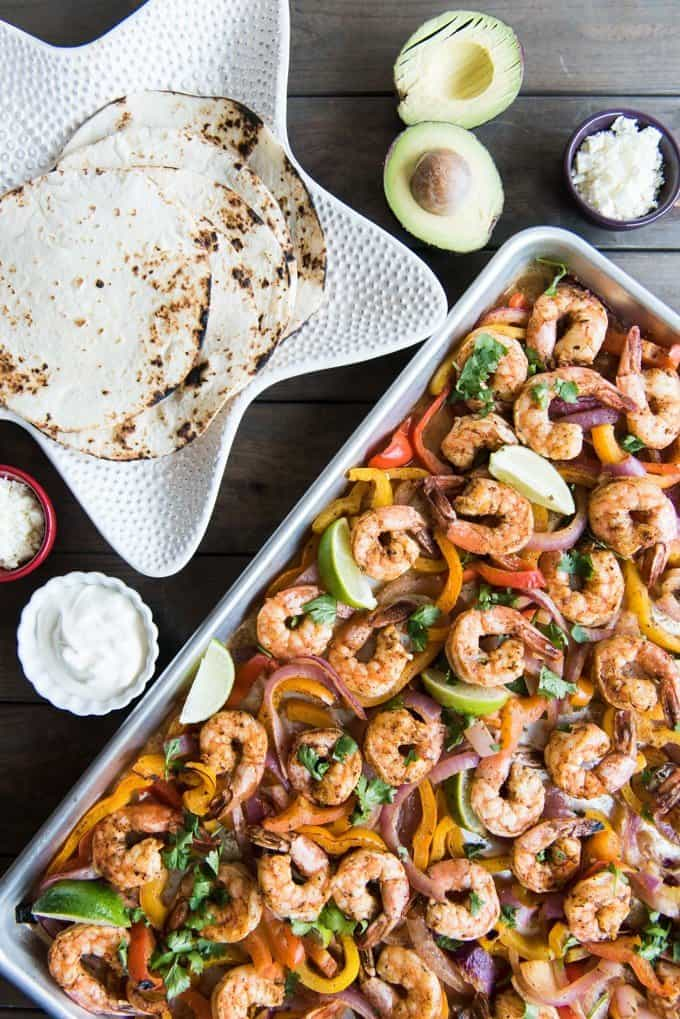 a star shaped bowl of tortillas and a baking sheet full of shrimp fajita filling