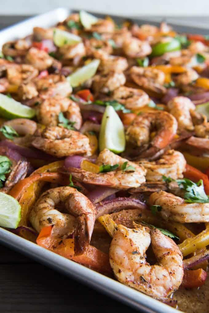 shrimp fajita filling and lime wedges on a baking sheet