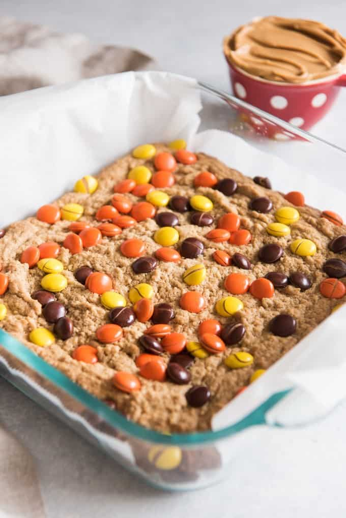 a glass 8x8 baking dish with peanut butter blondies topped with peanut butter reeses pieces