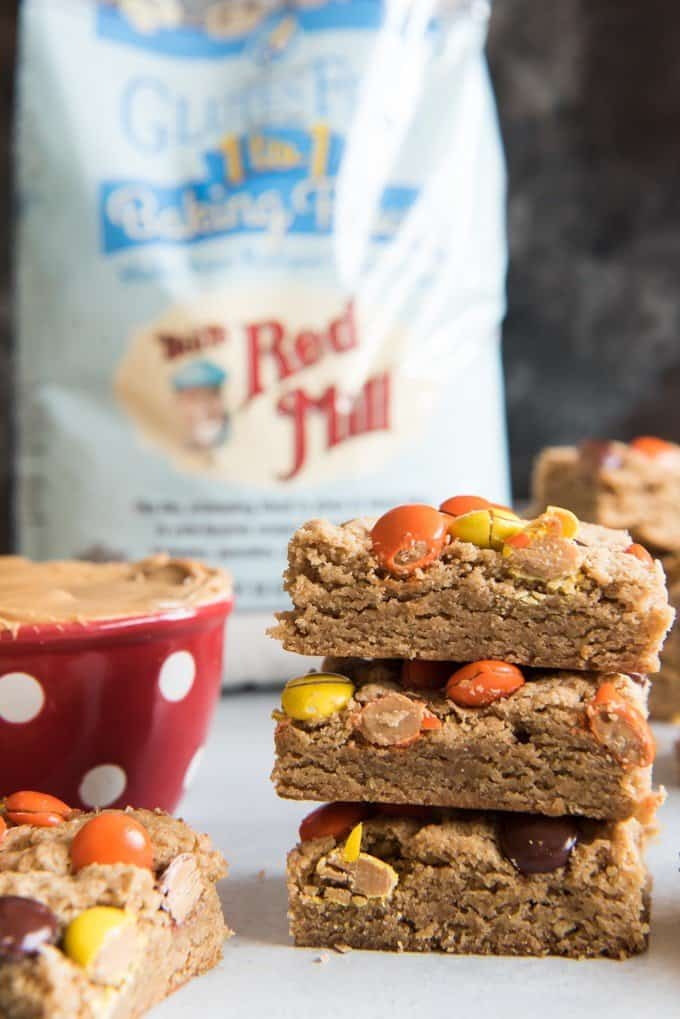 bobs red mill behind a stack of peanut butter blondies and a red and white cup of peanut butter