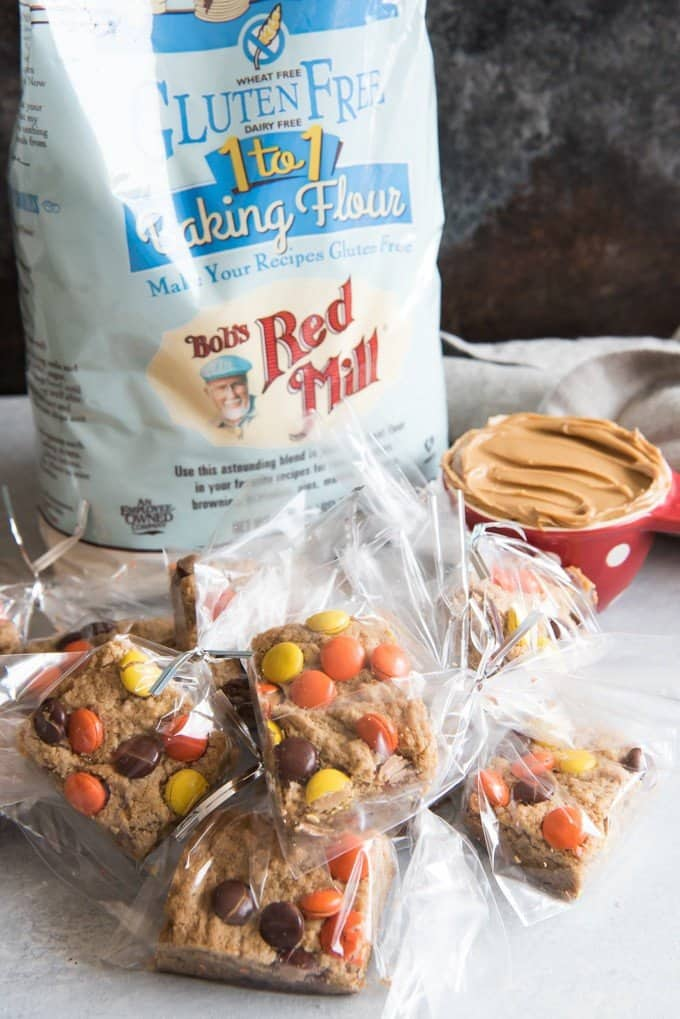 peanut butter blondies all in sealed treat bags next to a cup of peanut butter and a bag of bobs red mill