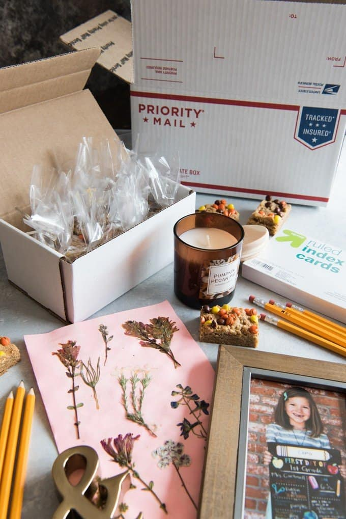 priority mail box and supplies around a candle jar and single peanut butter blondie