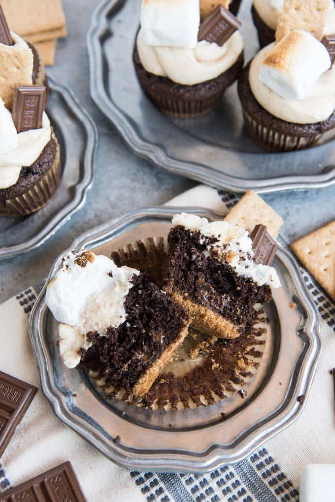 a sliced open chocolate smores cupcake with whole ones on plates around it