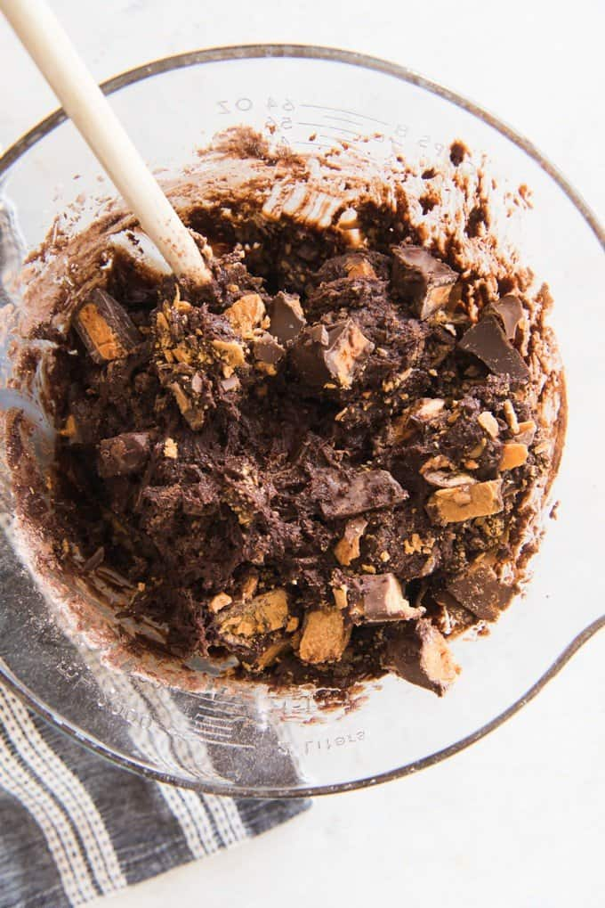 a bowl of butterfinger brownie batter and a wooden spoon