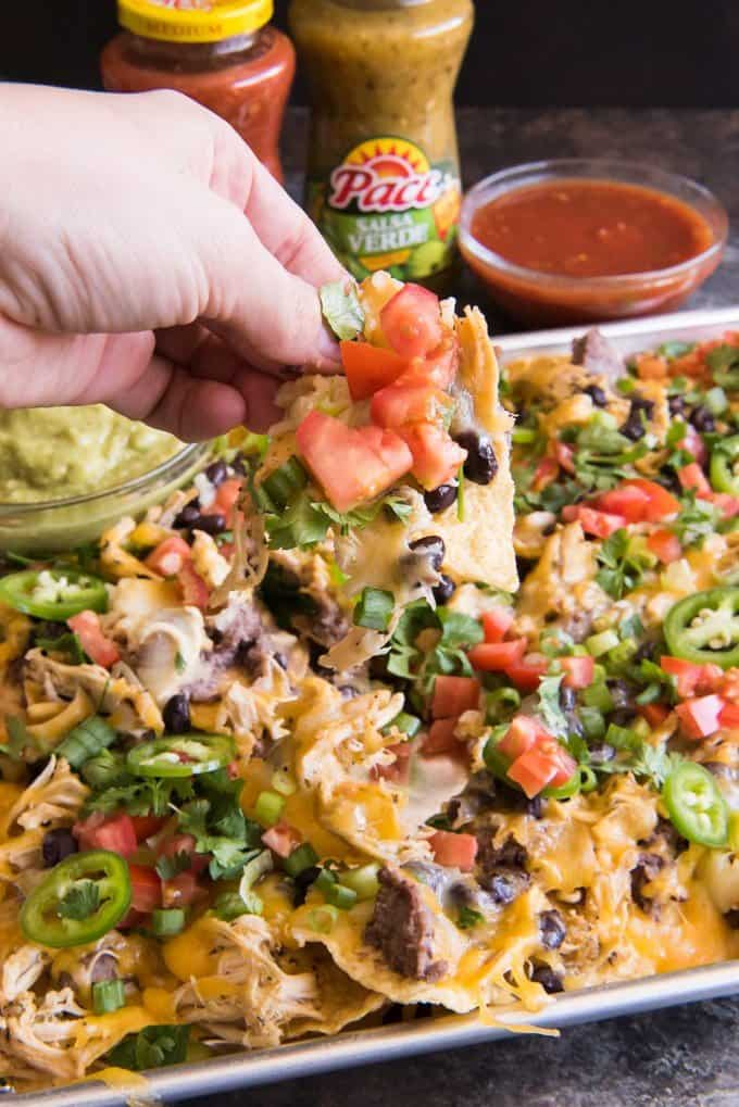 These Sheet Pan Ultimate Nachos with Slow Cooker Salsa Verde Ranch Chicken are the perfect Game Day food!  Get everything you need at Walmart and serve them with not one, but TWO easy sauce options for dipping the cheesy, loaded nachos in before devouring!