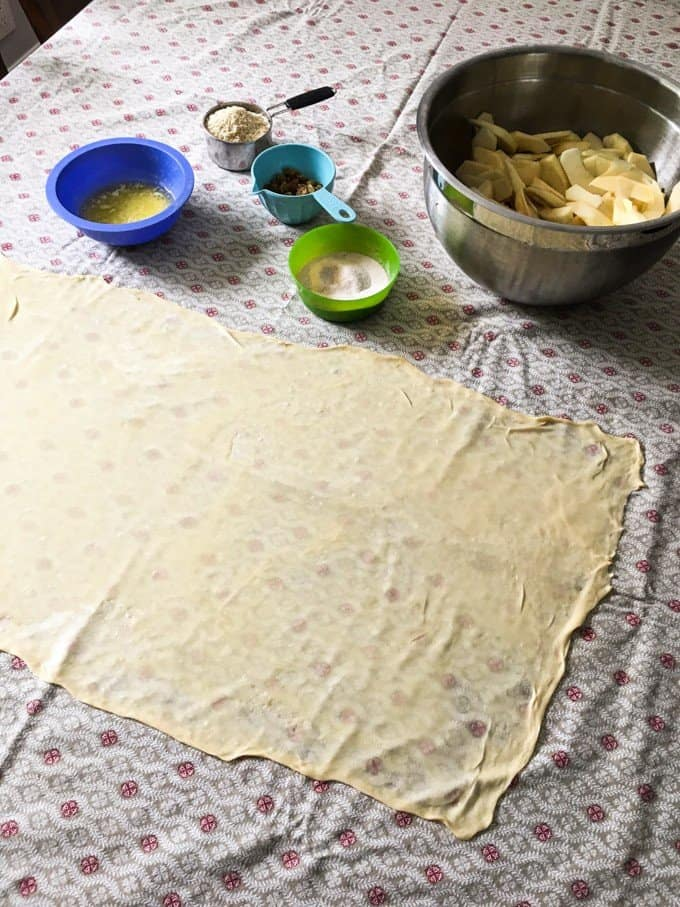 Ingredients to make german apple streudel with a dough rolled out into a rectangle so thin that you can see the tablecloth pattern through it