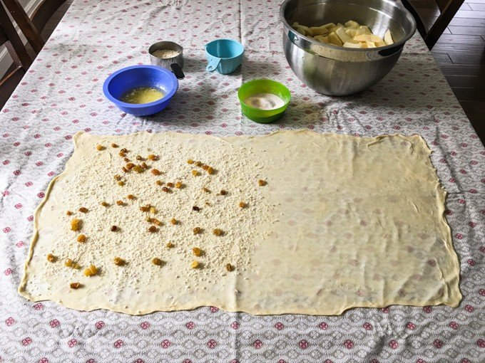 very thin rectangle of dough rolled onto a table cloth with other ingredents in bowls behind it. some ingredients have been sprinkled on half of the dough