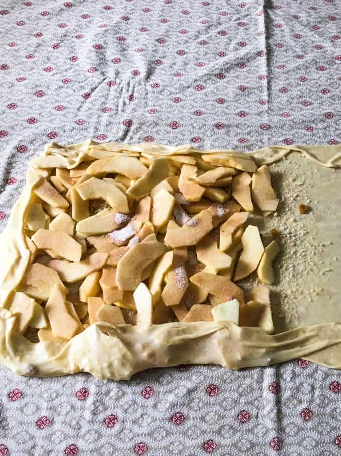 apple slices piles onto the thin rectangle of dough and some of the edges have been pulled up