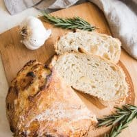 Roasted Garlic & Rosemary No Knead Artisan Bread on a wooden cutting board with fresh rosemary and garlic