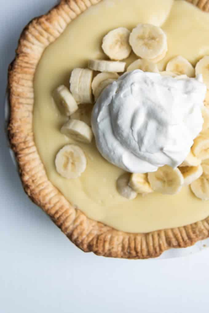 Old-fashioned banana cream pie with sliced bananas and a large dollop of fresh sweetened whipped cream on top.