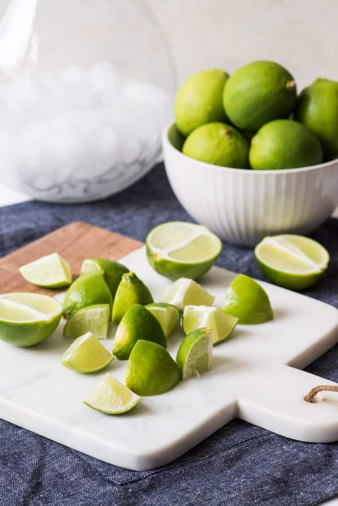 Fresh limes cut into 1/8ths ready to go into Brazilian lemonade with a pitcher of ice and a bowl of limes behind them.