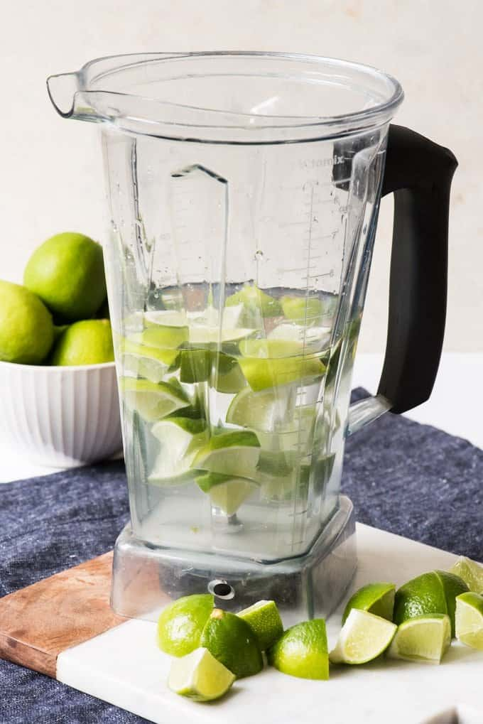 A vitamix blender with water, sugar and cut up limes, ready to be blended into Brazilian Lemonade.