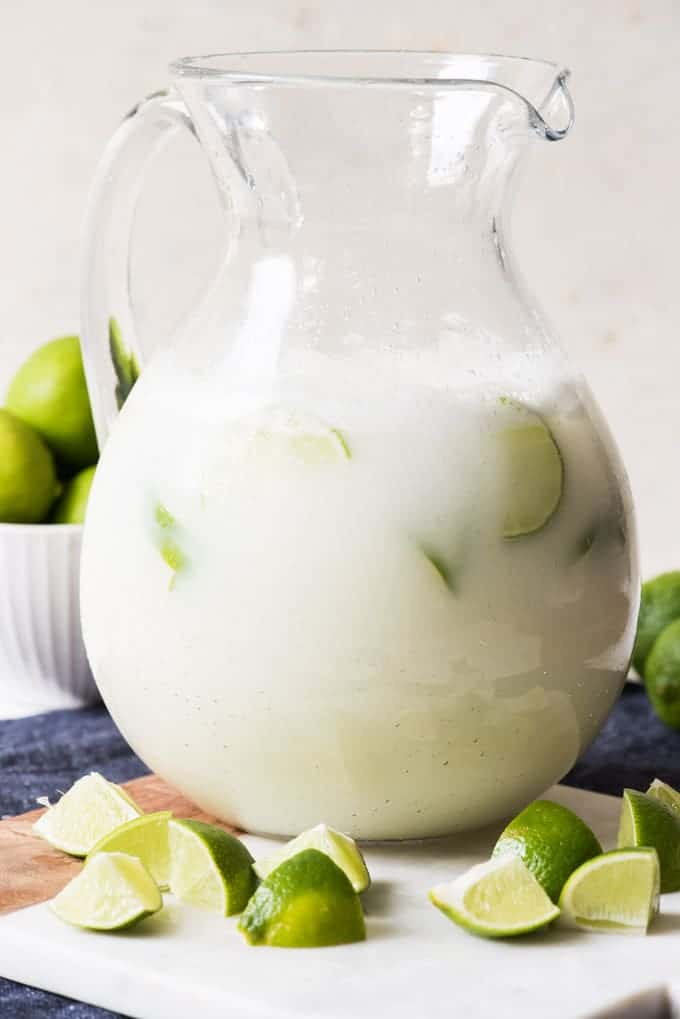Large glass pitcher full of Brazilian Lemonade (sometimes called Brazilian Limemade) with ice cubes and slices of lime floating inside and sliced chunks of lime on a cutting board in front of it.